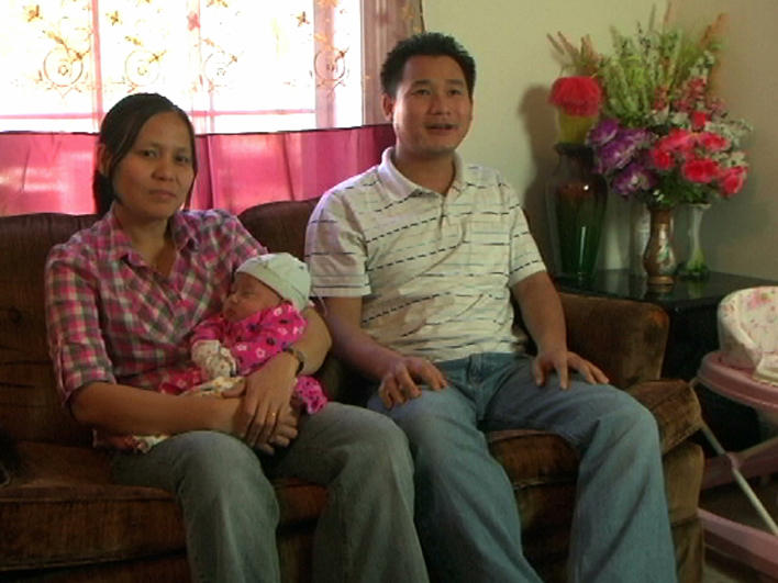 A couple with their baby at home