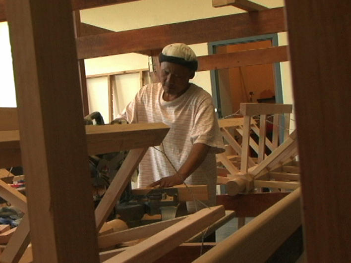 Man from Burma building a loom
