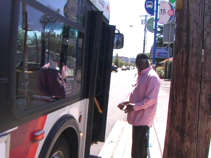 A senior refugee preparing to board a bus