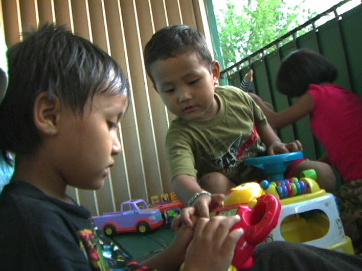 Children from Burma playing on apartment balcony