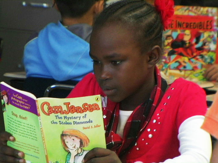 Darfuri girl reading at school