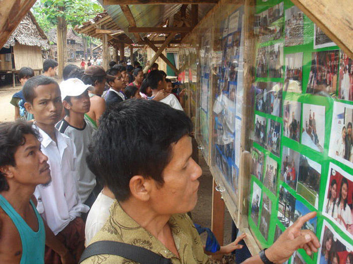 Refugees looking at the resettlement picture board