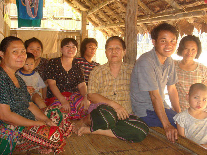 Refugees sitting on front porch in Mae La Camp